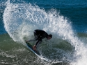 Surfer on a shortboard, doing a cutback